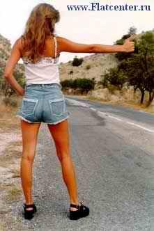 Девушка путешествует автостопом.Красивая девушка голосует на дороге