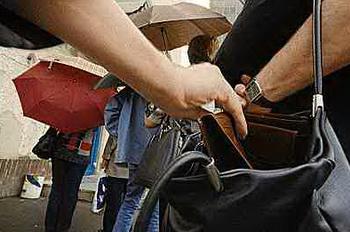 Карманник вытаскивает деньги у зазевавшегося туриста