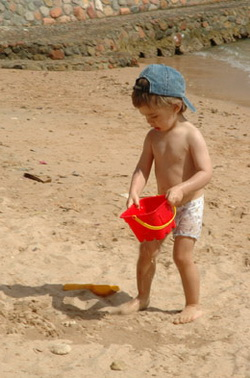 Маленький мальчик весело отдыхает на пляже