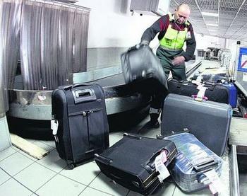 Служащий аэропорта перебирает багаж